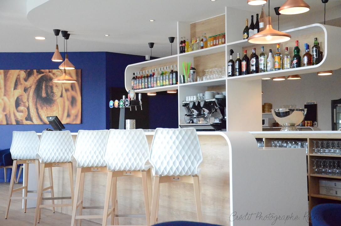 Brasserie mur bleu chaises relief suspensions cuivre