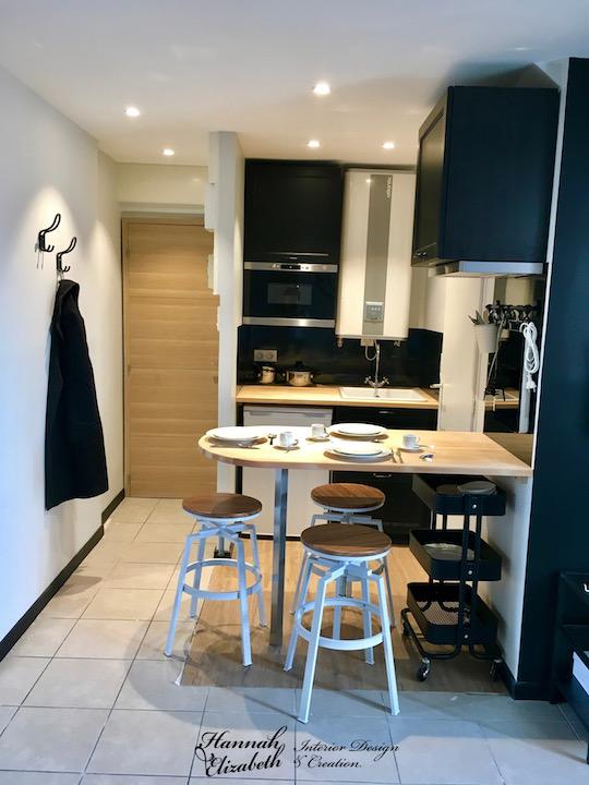 Cuisine et entree appartement studio noir blanc bois