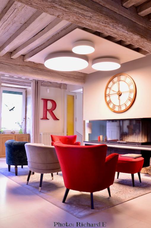 Poutres blanchi salon cheminee contemporain fauteuils rouge velours plafonniers rond hannah elizabeth interior design