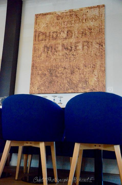 Salle brasserie fauteuils bleu tableau cuivre