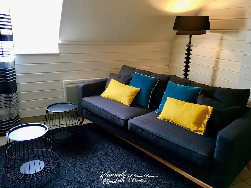 Salon appartement studio tapis jute noir canape gris coussins bleu jaune