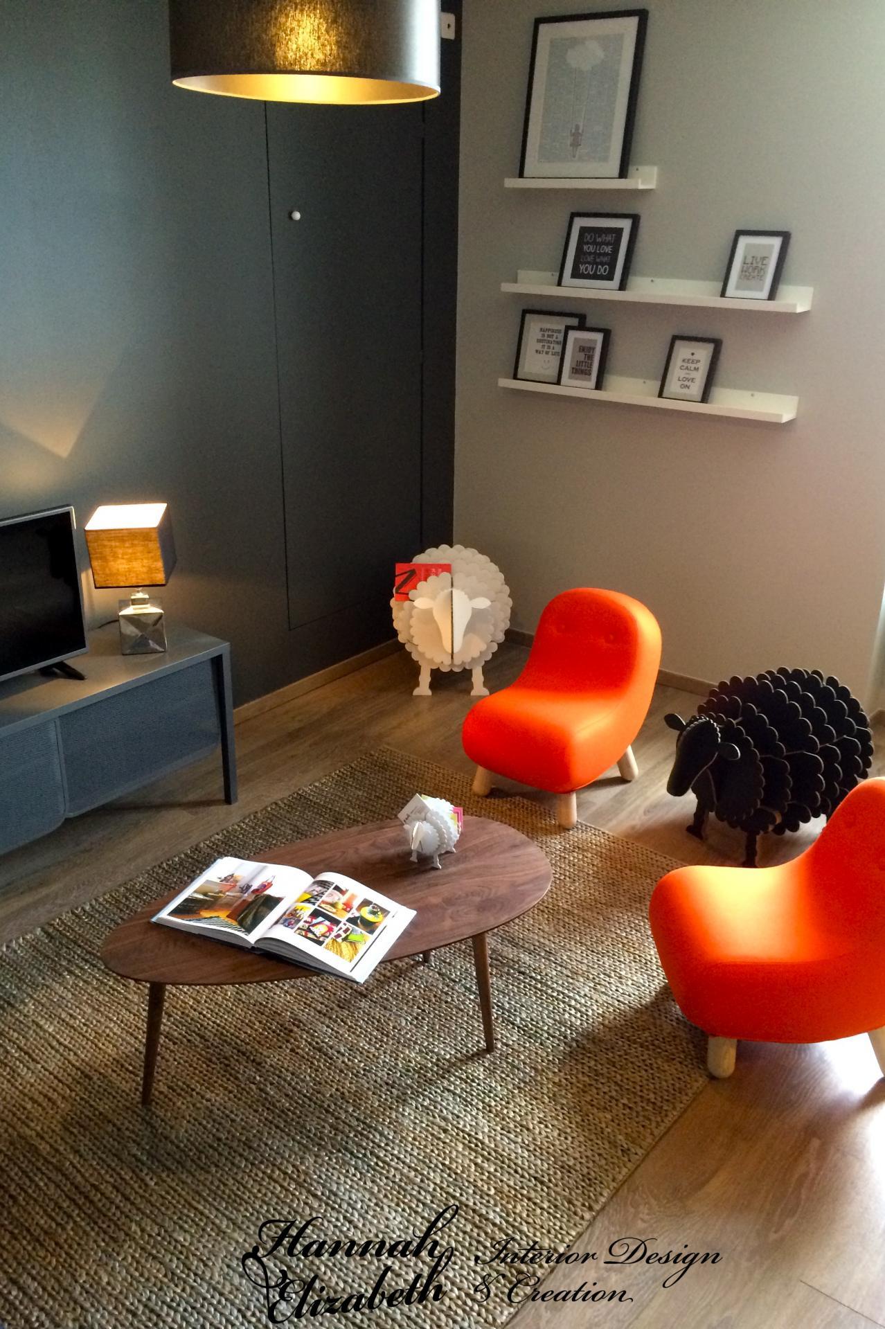 Salon cadres muraux moutons fauteuils orange bob tapis tresse