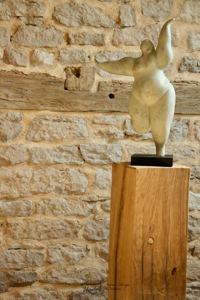 Statue sur totem bois devant mur pierre hannah elizabeth interior design