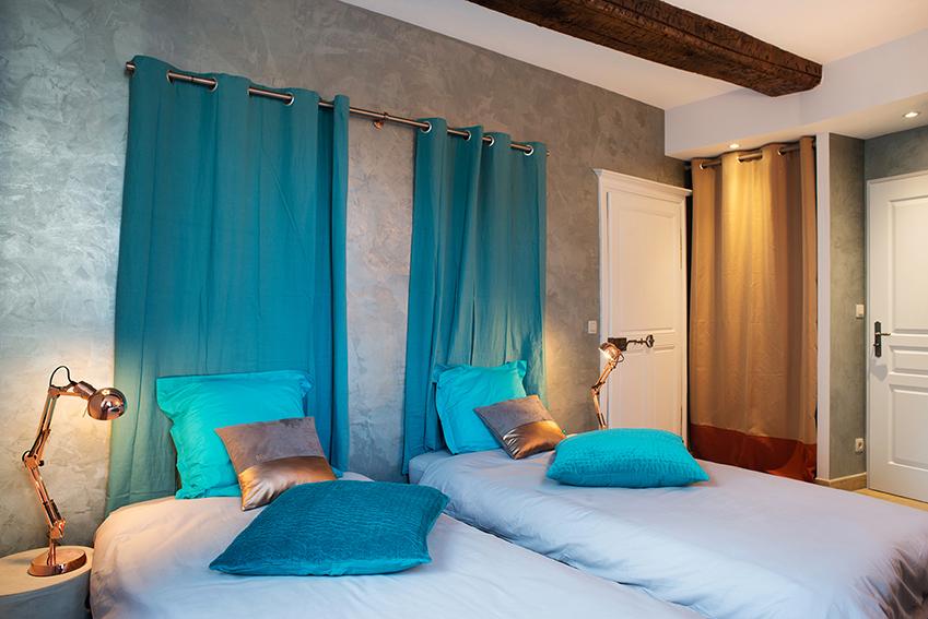 Tete de lit enduit gris et rideaux turquoise